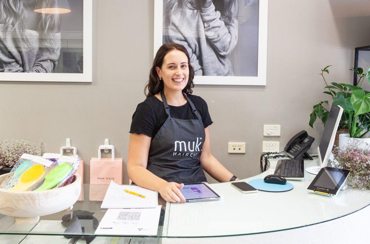 Smiling salon receptionist behind desk